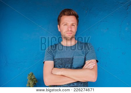 Portrait Of Smiling Young Caucasian Man Standing Near Blue Wall With Freen Leaf. Concept Of Comfiden