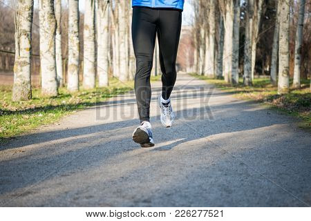 Close-up Photo of Male Legs Running in the Park in Cold Sunny Autumn Morning. Healthy Lifestyle and Active Sport Concept.