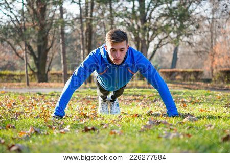 Young Male Runner Doing Push Up on the Green Lawn in the Park in Cold Sunny Autumn Morning. Healthy Lifestyle and Active Sport Concept.