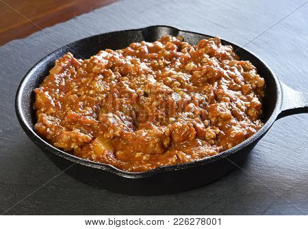 Bolognese Sauce In A Cooking Pan Or Iron Pan. Italian Cuisine Background With Pasta Sauce And Slate