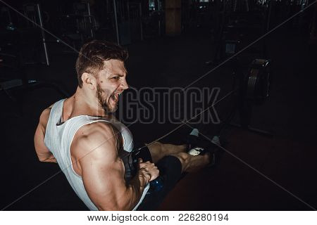Fitness Young Man Using Rowing Machine In The Gym And Screaming Hard