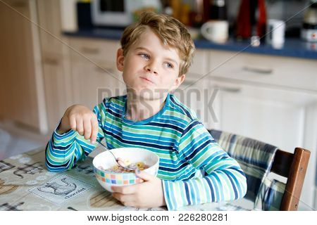 Adorable Little Blond School Kid Boy Eating Cereals With Milk And Berries For Breakfast Or Lunch. He