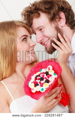 Loving Couple With Candy Bunch Bouquet Flowers. Man And Woman Holding Present Gift.