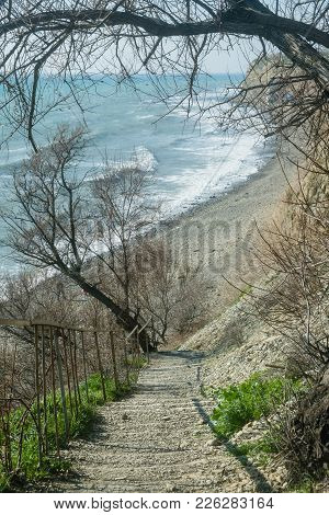 A Stone Staircase On A Steep Mountain Slope Above The Sea. Trees, Plants, Winter At Sea.