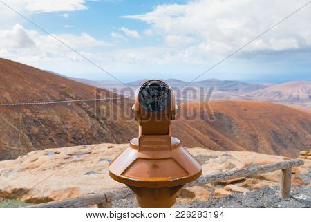Coin-operated Binoculars On Scenic Outpost With Mountain Range And Partially Cloudy Sky In Backgroun