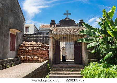 Hanoi, Vietnam - July 17, 2016: Aged Church Gate With Holy Cross On Top, Vietnamese Old Woman Wear C