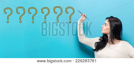 Question Marks With Young Woman Holding A Pen On A Blue Background
