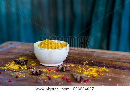 Close Up Bright Turmeric Powder In White Bowl On Wooden Table Covered With Anise And Pink Peppercorn