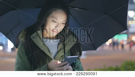 Woman sending audio message on cellphone and bringing black umbrella at night