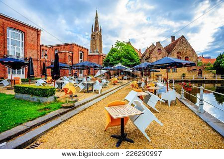 Bruges, Belgium - June 10, 2014: View Of Outdoor Cafe In Church Of Our Lady In Bruges. Its Tower, At