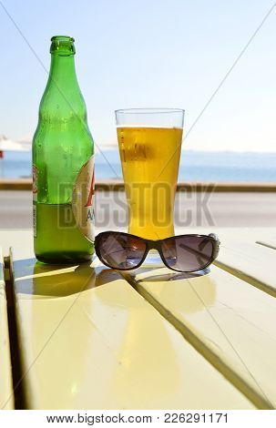 Ipsos, Corfu, Greece - October 5, 2017 : Ipsos Beach Bottle Of Beer With Glass And Sunglasses