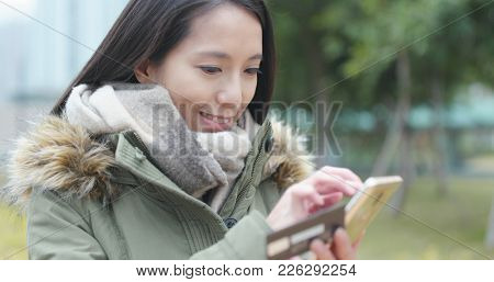 Woman use of mobile phone for online shopping at outdoor