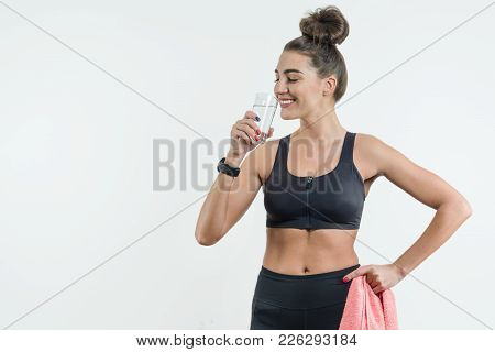 Positive Smiling Fitness Woman Drinking Water Against A White Background. Sport, Fitness, Wellness A