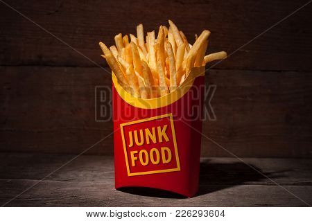 French Fries In Red Paper Packing With Words Junk Food On A Wooden Table