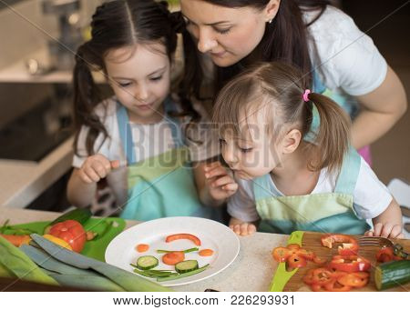 Happy Family Mother And Child Daughter Are Preparing Healthy Food, They Improvise Together In The Ki