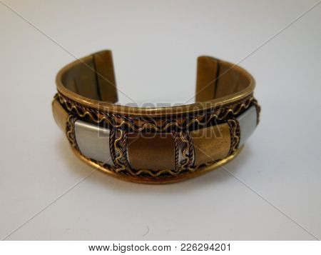 Indian Bracelet Made Of Brass With Multi-colored Metal Inserts Lies On A White Background