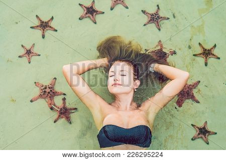 Young Woman In The Sea With Red Starfishes