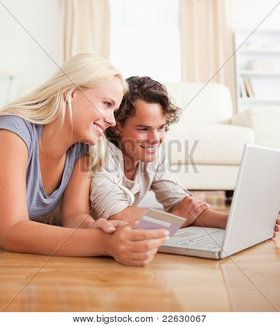 Cute couple purchasing online in their living room