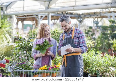 Gardener Using His Digital Tablet To Advise A Female Client Who Buys Flowers