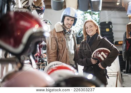 Handsome Couple Choosing A Trendy Motorcycle's Helmet In A Speci