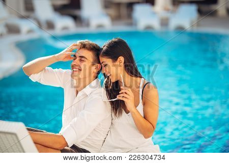Loving Couple Spending Vacation On Tropical Resort Swimming Pool.newlyweds Honeymoon On Seaside.coup