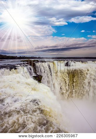 Devil's Throat is the part of the Iguazu Falls. The autumn sun shines through the clouds. Concept of active and photographic tourism