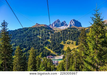 Picturesque valley in the Italian Dolomites. The coniferous forests at the foot of limestone rocks. The most beautiful route in the Italian Dolomites. The concept of active and car tourism