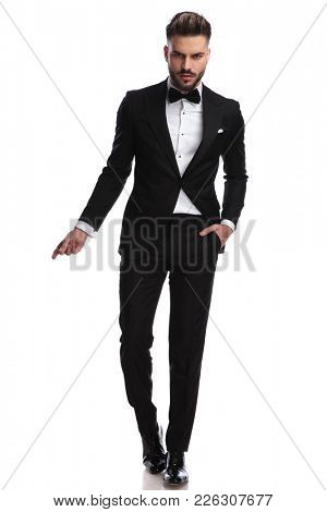 cool dramatic man in tuxedo snapping fingers and stands on white background