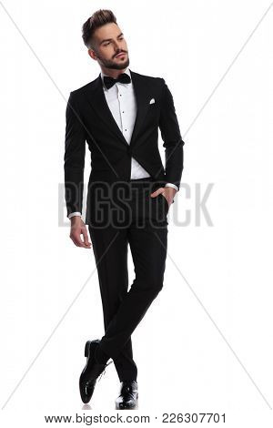 elegant young man in tuxedo standing with hand in pocket and looks to side away from the camera on white background