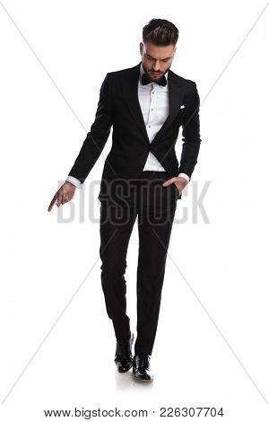 elegant man in tuxedo snapping fingers and looks down on white background