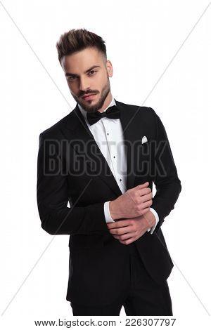 elegant man in tuxedo fixing his sleeve on white background