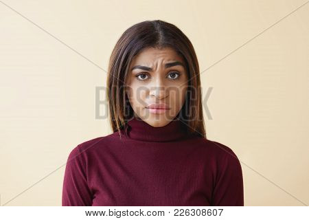 Studio Shot Of Grumpy Frowning Mixed Race Girl With Straight Dark Hair Staring At Camera With Suspic