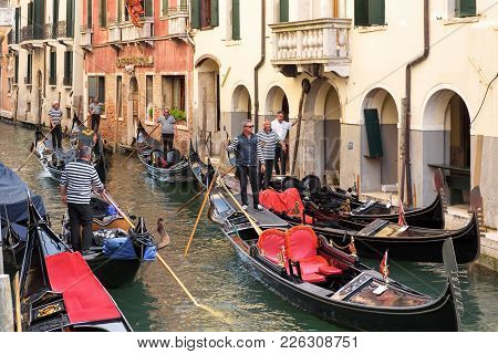 Venice, Italy - May 18, 2017: Gondoliers With Gondolas Expect Tourists In Venice. Gondola Is The Mos