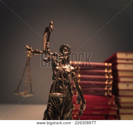justice statue in front of a pile of law books in studio