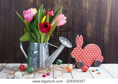 Bunch Of Spring Bright Tulips In Galvanized Watering Pot And Easter Eggs. Easter Greeting Card With