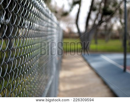 Chain Link Fence Around Basketball Courts In Park