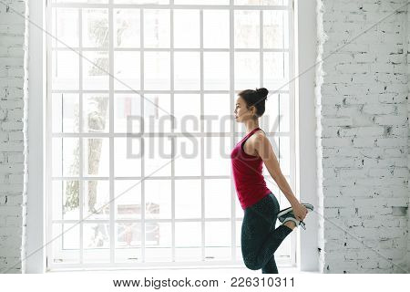 Muscular Fit Young European Female Athlete Doing Standing Quadricep Front Thigh Stretch On Her Legs