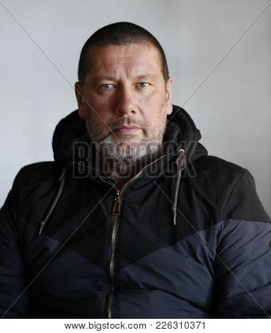 Brutal Man  Of 40 Years Old With A Gray Beard In A Jacket With A Zipper With A Hood Looking Directly