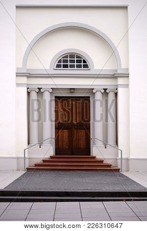 The Entrance Of A Newly Built And Modern Church With An Entrance Door With Round Arch And White Wall