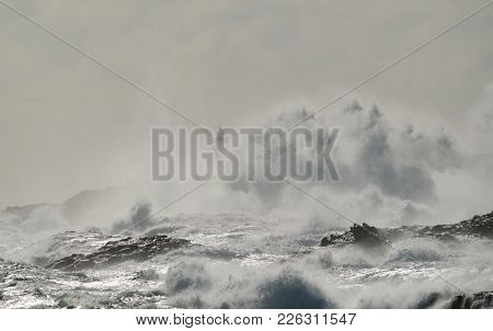 Rough Sea, Big Wave When Breaking On The Coast And Silhouette Of Lighthouse In Background, Telde, Ca