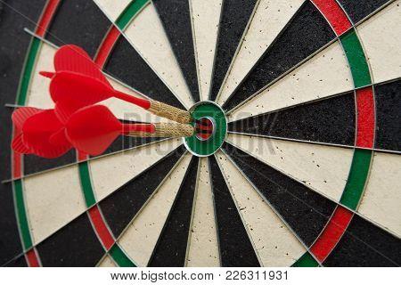 Close Up Of Three Darts In Bull's Eye