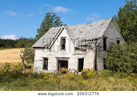 Derelict house in New Brunswick, Canada. Front angled view with overgrown meadow and summer sky.