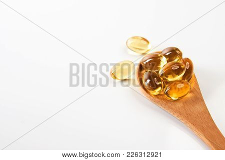 Cod Liver Oil Omega 3 Gel Capsules In A Wooden Spoon On White Background Fish Oil Pills Close-up. Me