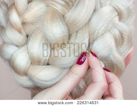 Beautiful Girl With Blonde Hair, Hairdresser Weaves A  Braid Close-up, In A Beauty Salon. Profession