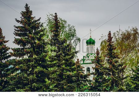 Beautiful Church Of St. John The Baptist Monastery Between Fir Trees At Overcast Weather.