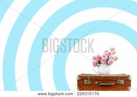 Pink Flowers In Jug On Old Brown Vintage Suitcase.
