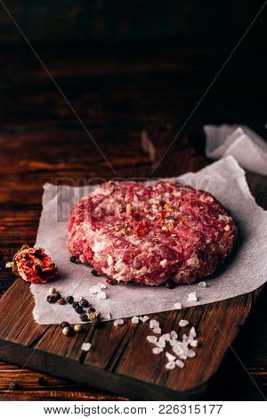 Raw Round Patty With Peppercorns, Salt And Chili Pepper On Wax Paper For Burger.
