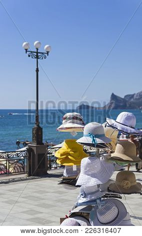 A Hanger With Female Summer Hats In A Store On The Waterfront Of The Resort Town Of Sudak. Crimea, A