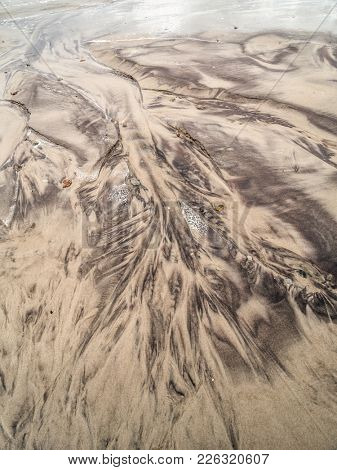 Tidal watercourse and marks in wet sand on the beach