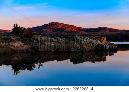 The Sky And Rocky Edge Reflects In The Still Water In The Early Morning At Wichita Mountains Nationa